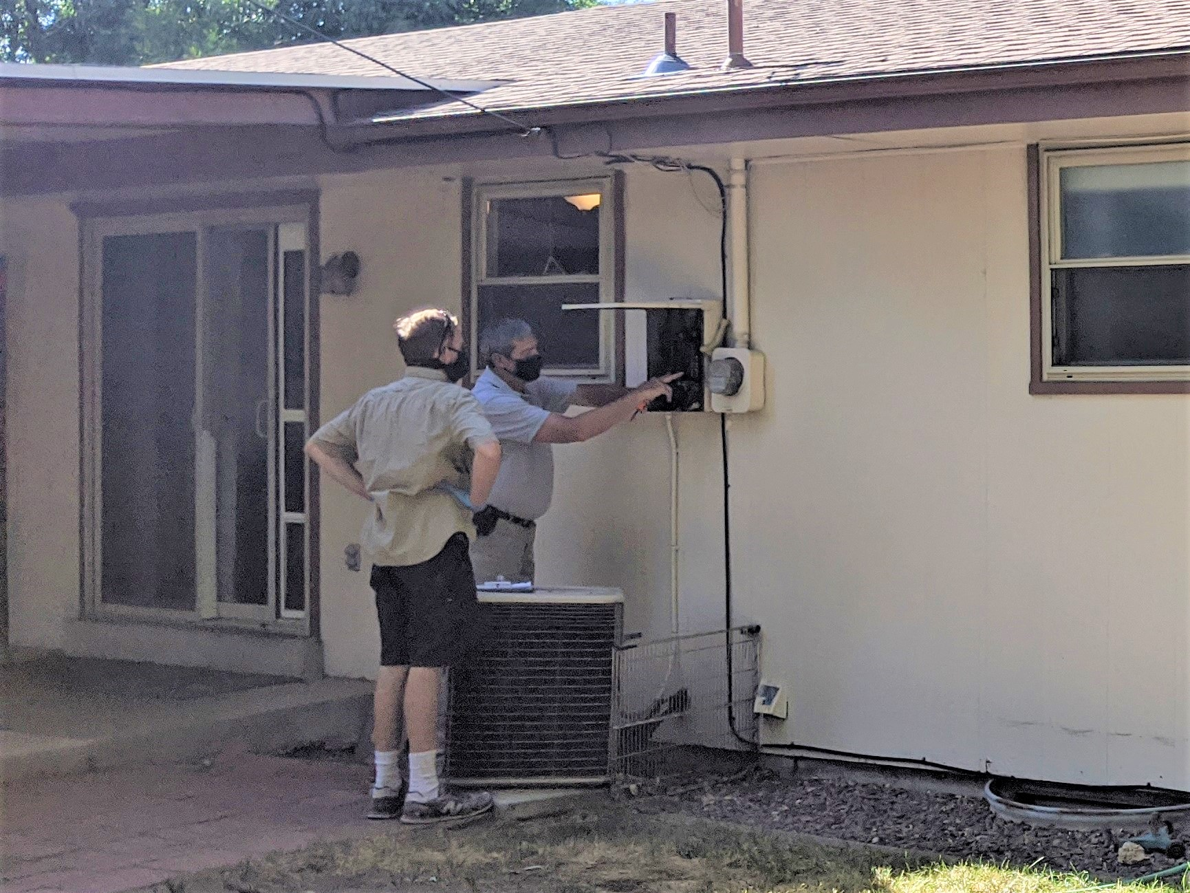 The home inspector explains to the homebuyer what he notices about the main electrical panel.