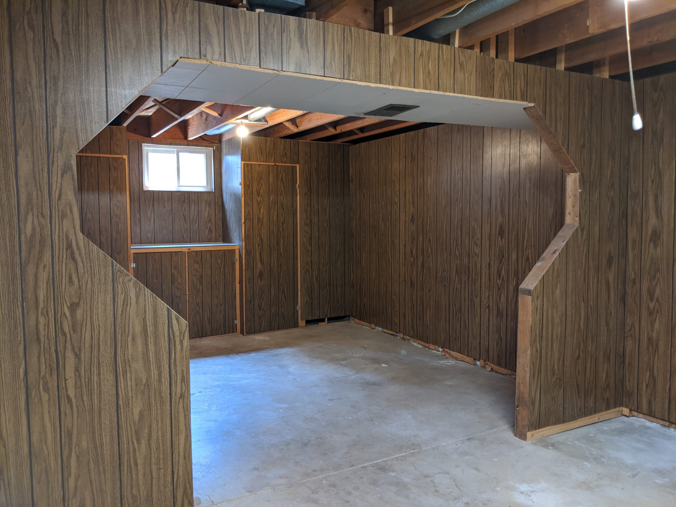 """With dated paneling, exposed ceiling, and raw cement floors, this unfinished basement was the """"diamond in the rough"""" we were looking for. We'll add instant value to our first house by renovating it. (On the plus side, those cabinets provided functional storage.)"""