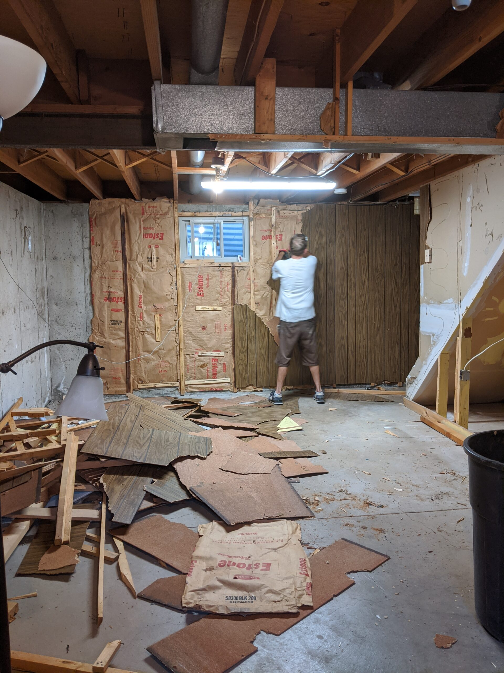 Josh pulled down the paneling, moisture vapor barrier paper, and old lumber.