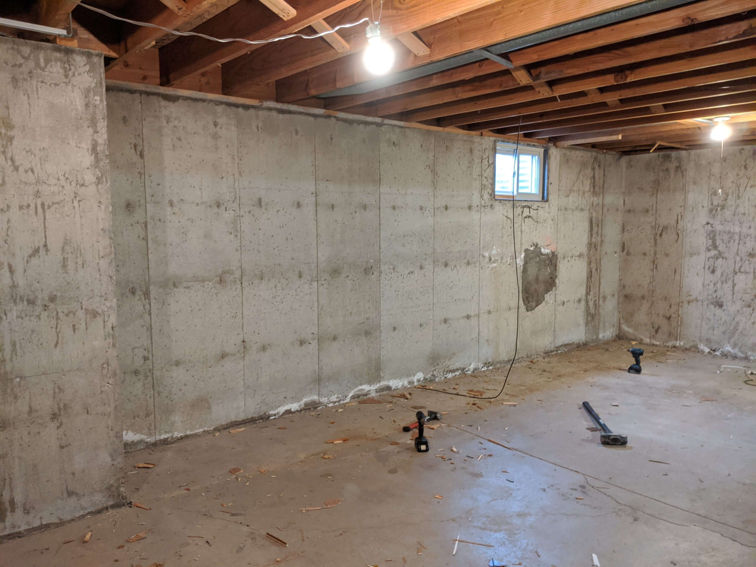 Finally! The cabinets, shelves, paneling, and moisture vapor barrier are all removed to expose the raw foundation walls. The dark spot under that window is a properly completed concrete patch -- and future spot of an egress window to create 1 of 2 legal bedrooms in the basement.