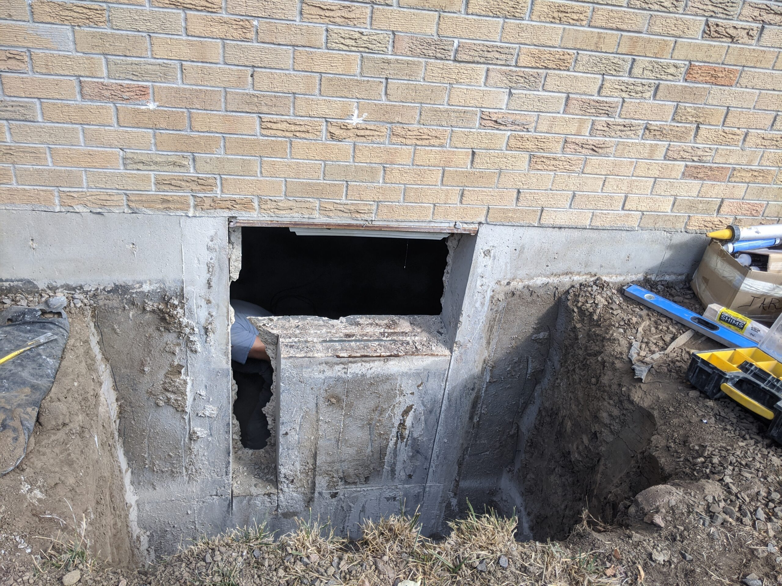 IN PROGRESS: This window well was dug deeper and a bigger hole was cut in our house's foundation to convert this opening to a legal egress.