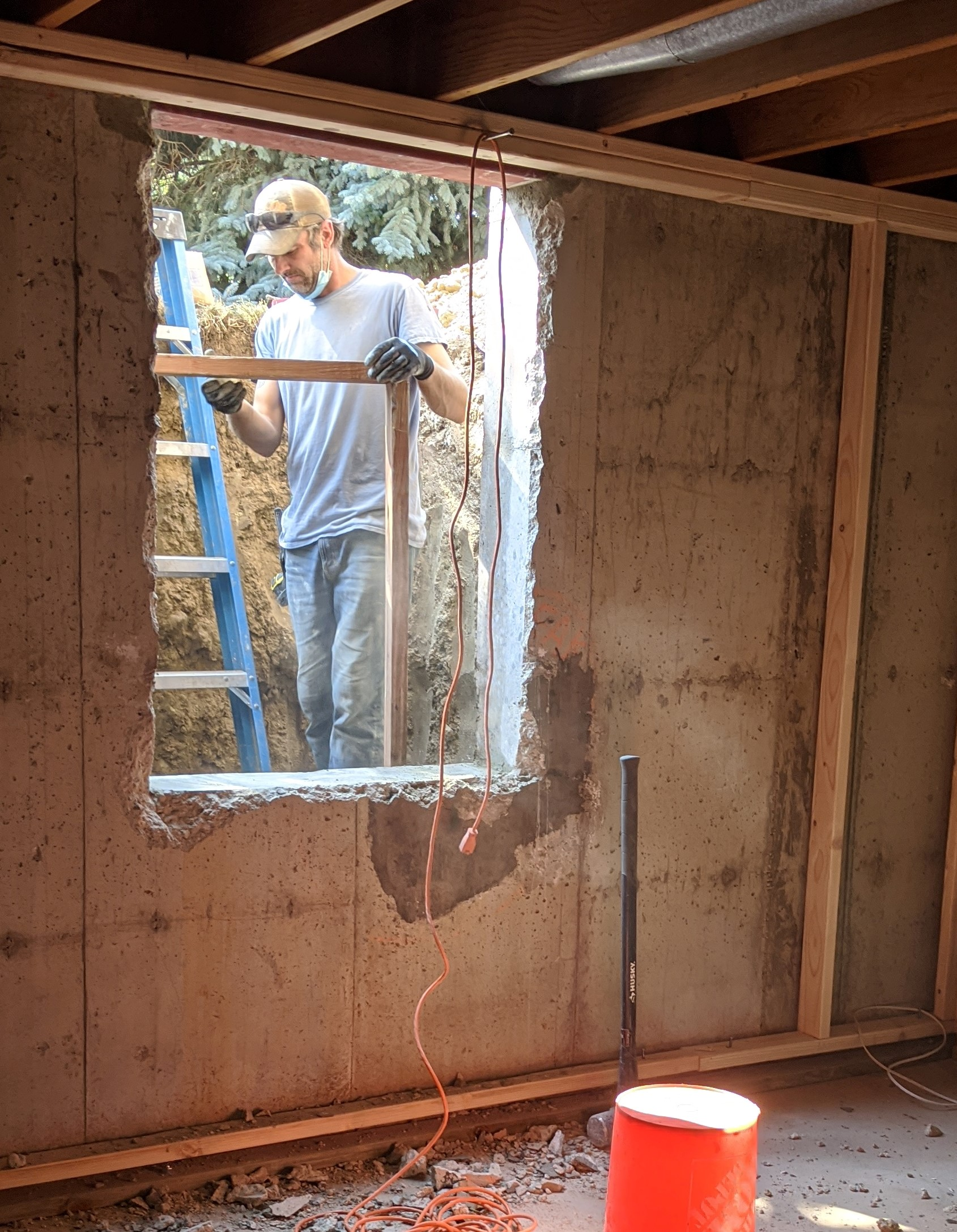 """IN PROGRESS: After the 9 ½"""" thick foundation wall was cut with a concrete saw, the center of the hole was knocked out with a sledgehammer. Then, a frame was added to structurally reinforce the hole before the new window is installed."""