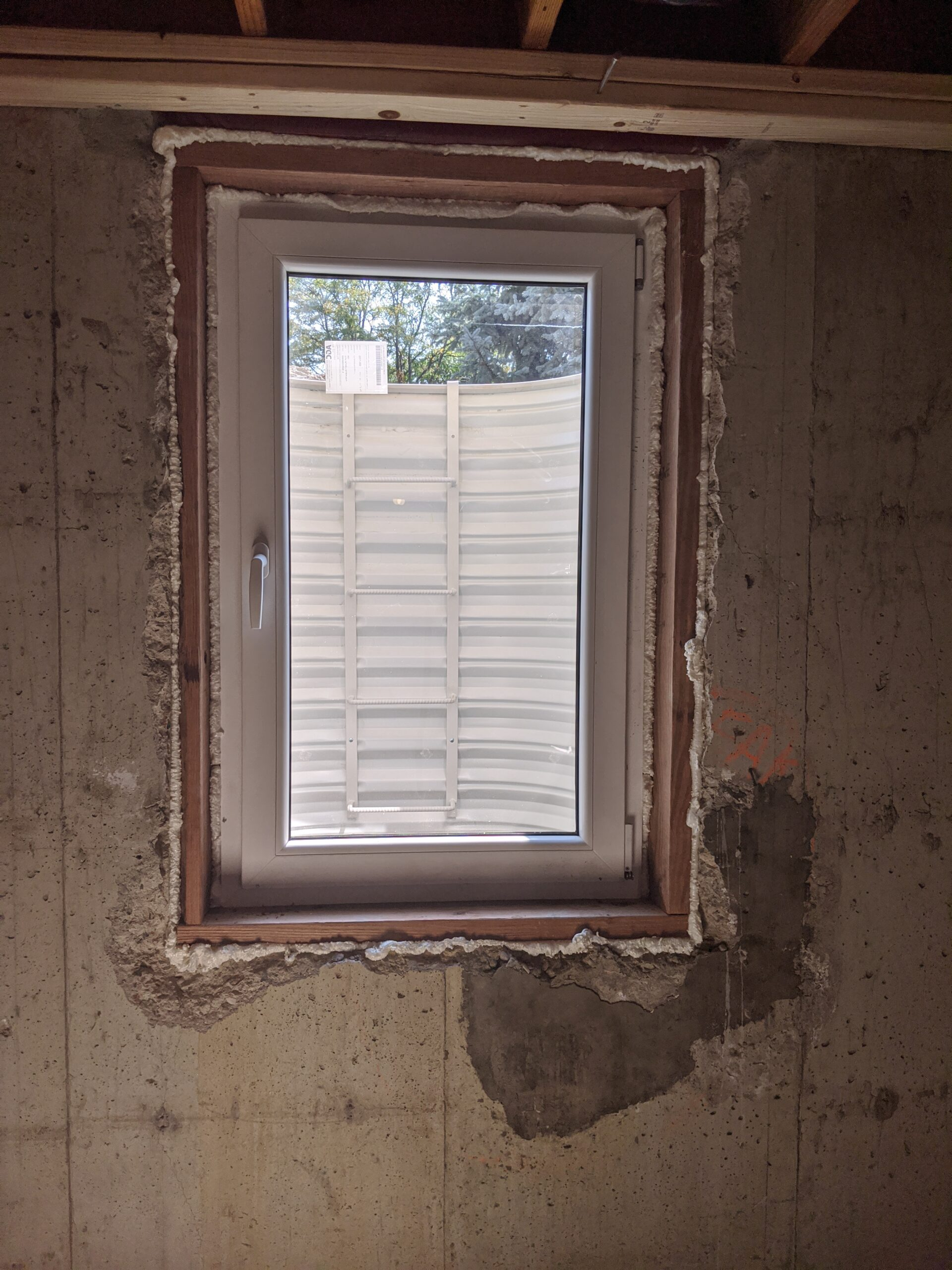 AFTER: Foam insulation fills gaps between the egress window and foundation to keep insects and moisture out, while keeping in heat or air conditioning.