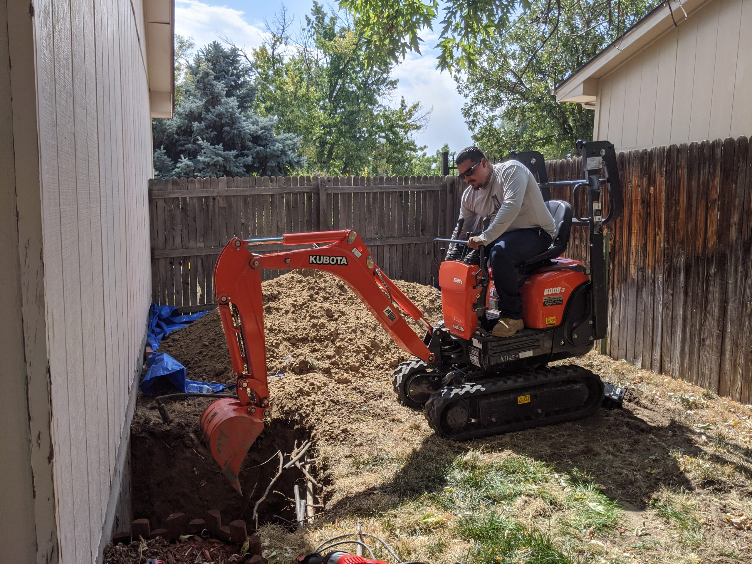 IN PROGRESS: An excavator was used to efficiently dig deeper window wells for both egress windows. Denver Egress Window made a neat pile of dirt next to the new hole so that they could easily use it to fill in around the new window well walls.