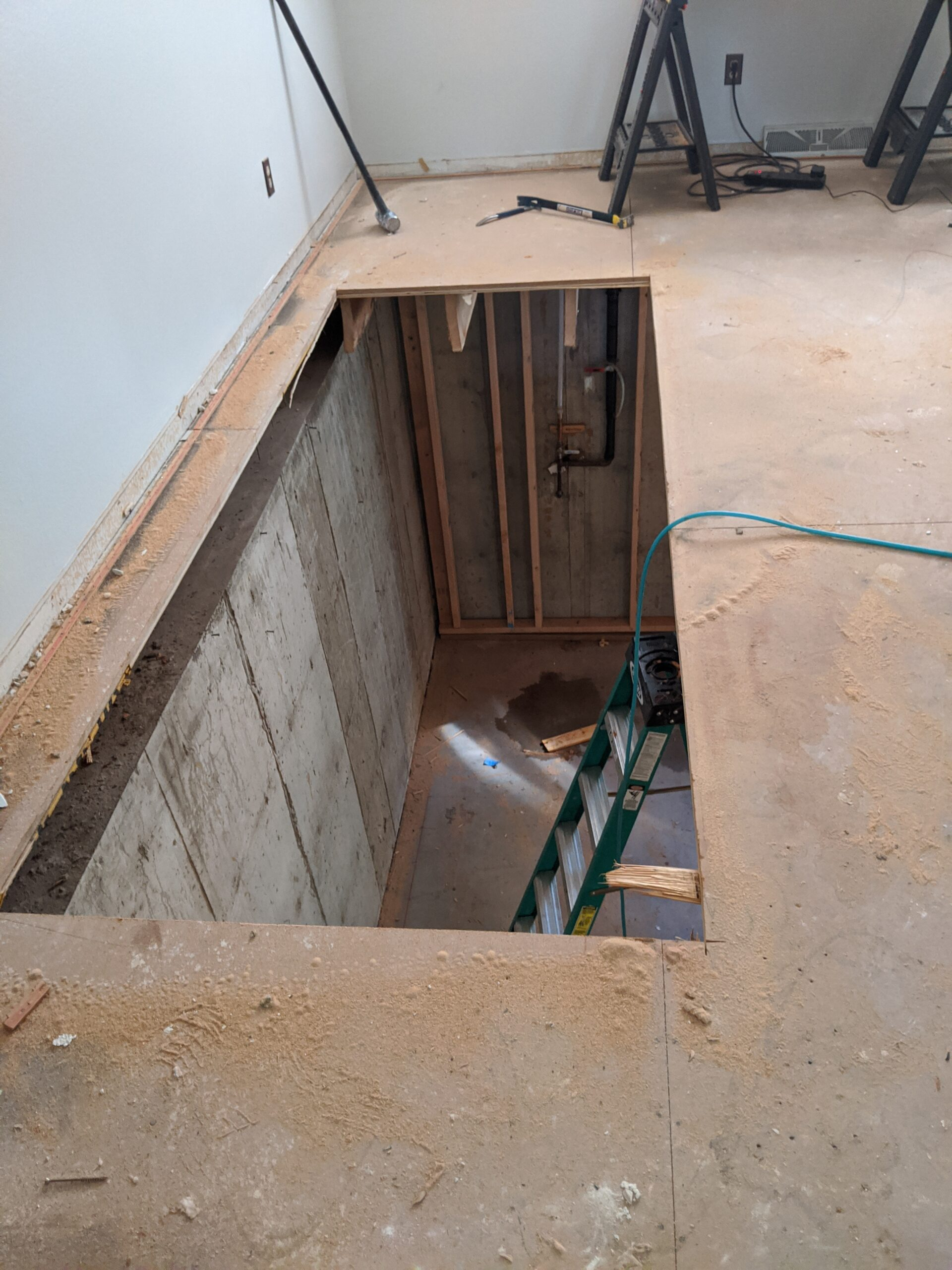 IN PROGRESS: The original stairs will be moved along the basement floor from the middle of the house to this new hole in the living room subfloor.