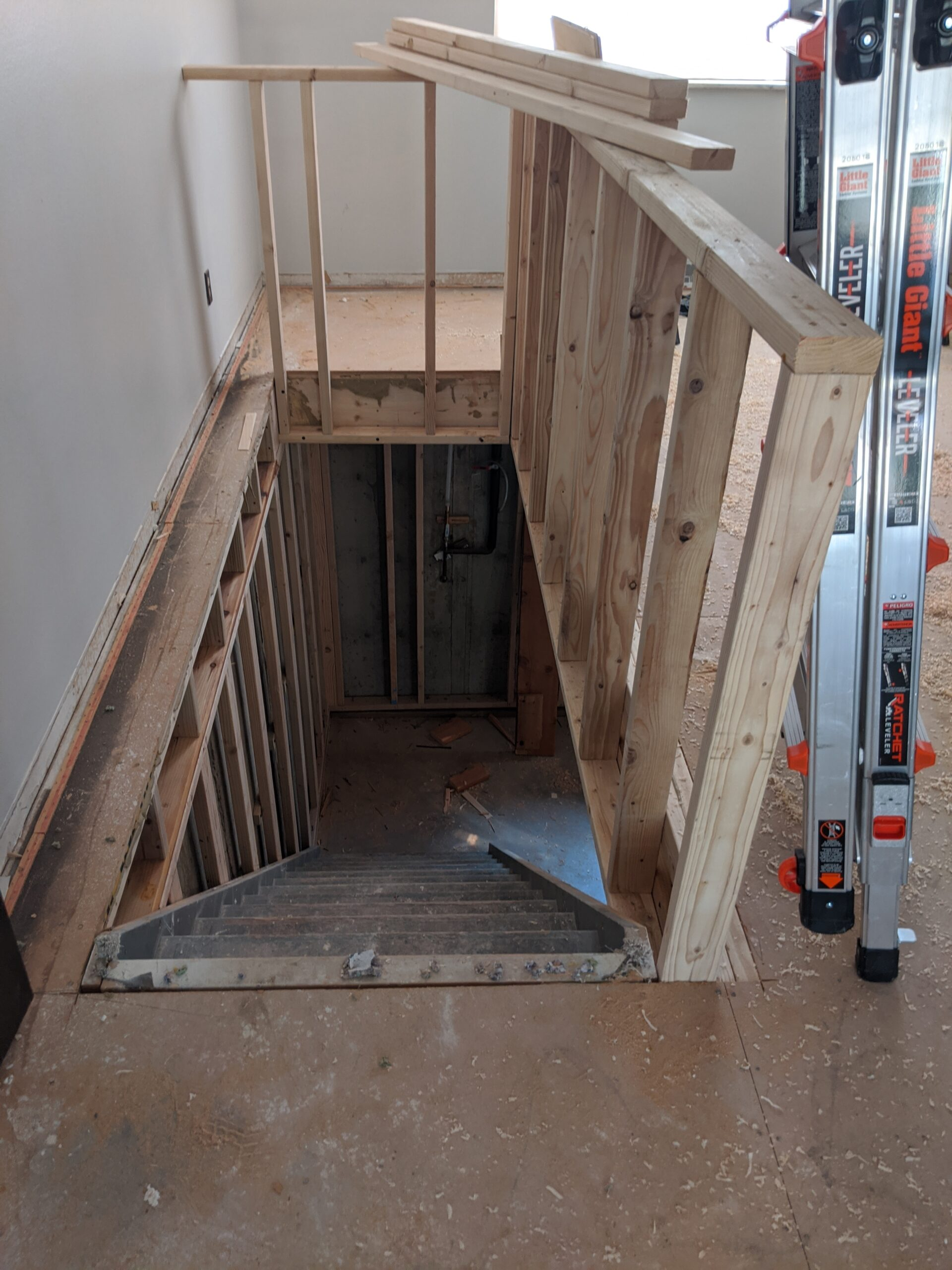 IN PROGRESS: He built a new half-wall around the stairs so the abundant natural light from that south-facing picture window isn't blocked.
