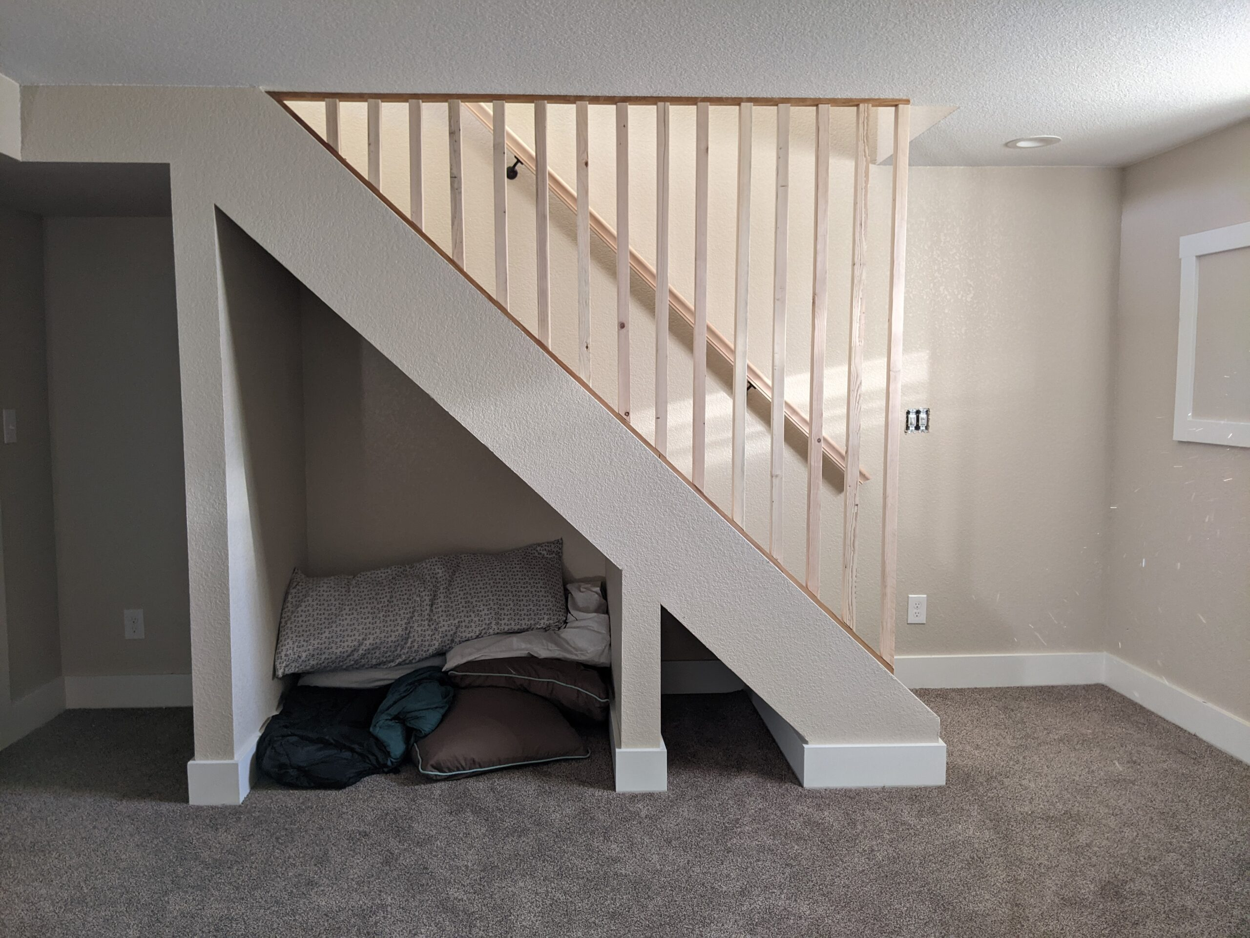 AFTER: We brought more natural light in the basement by lowering the well wall for a small, south-facing basement window. (Notice the light on the wall.) We also built a family room storage space below the stairs on the left and a small, carpeted pet nook on the right.