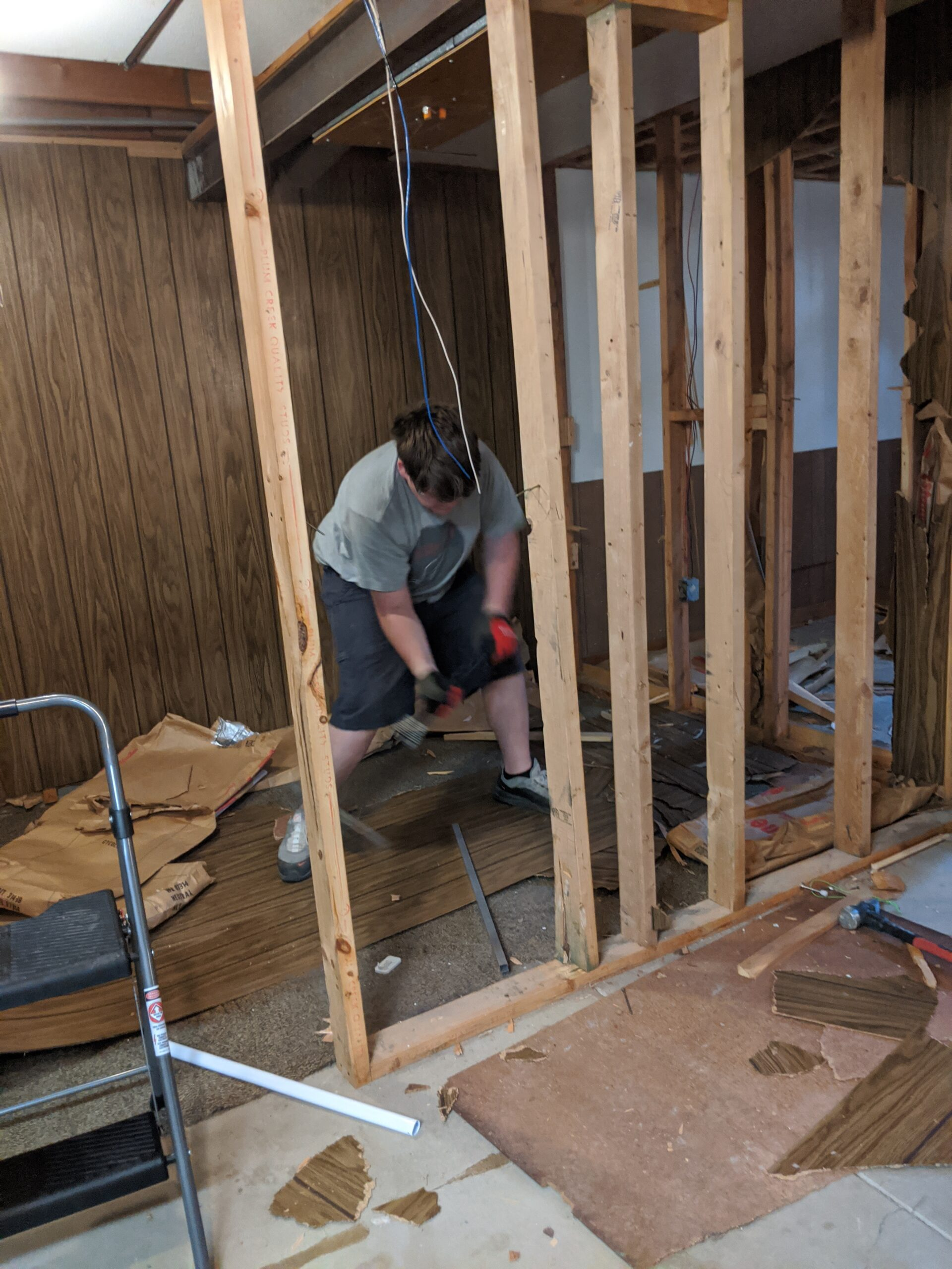 IN PROGRESS In our first round of demolition, we removed the wood paneling & framing of the basement walls.