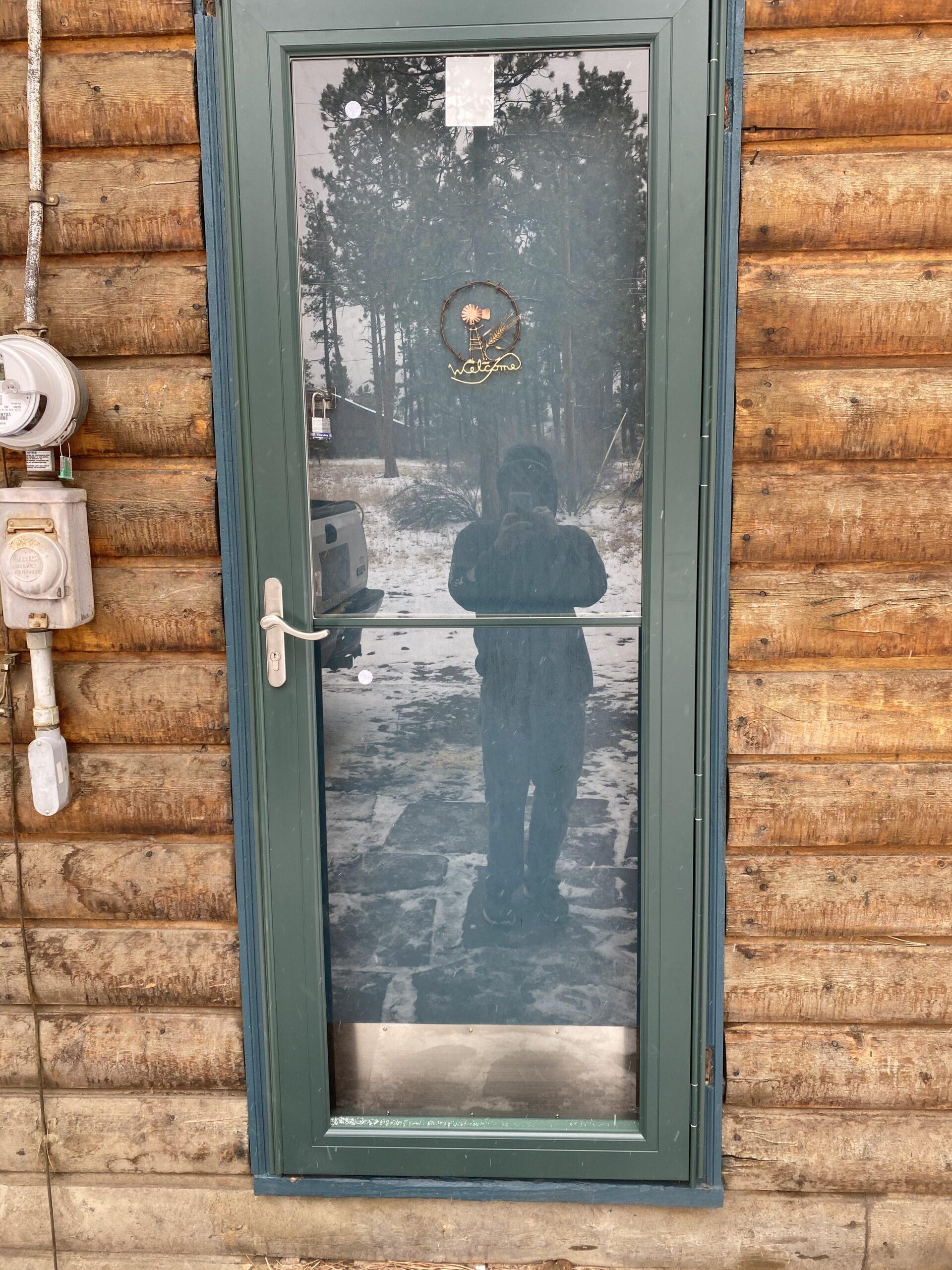 Metal storm door in log cabin