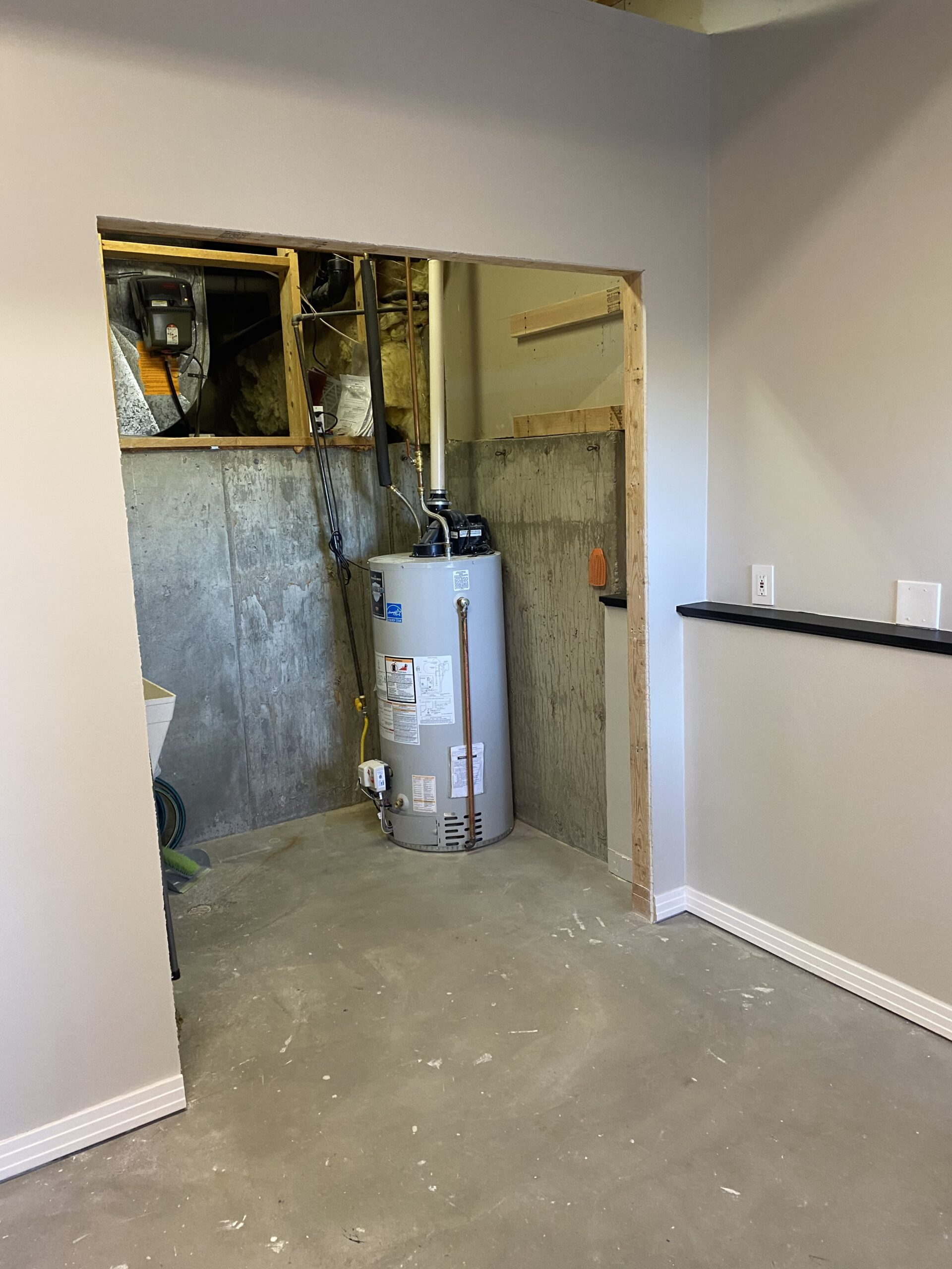 Water heater in unfinished utility closet with cement floors and framed doorway without doors