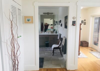 Framed doorway without a door into bathroom with vanity and mirror