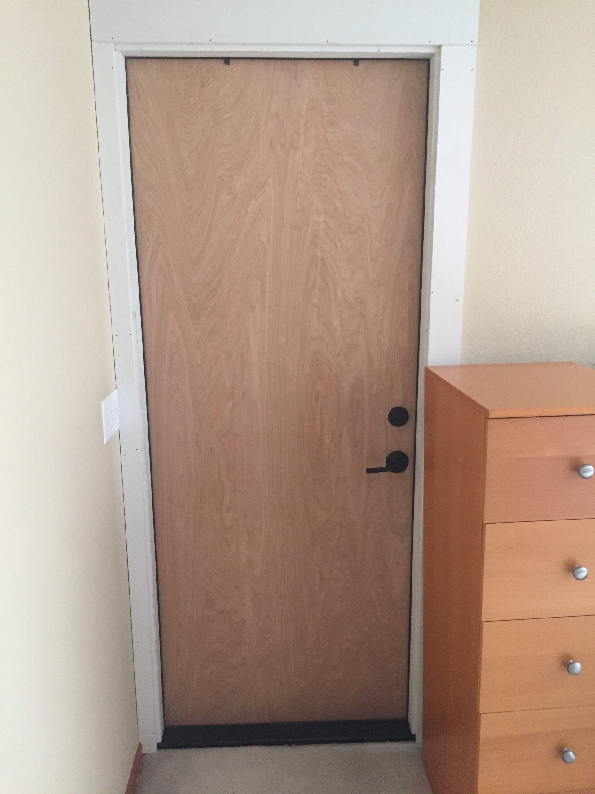 Solid wood door and trim next to dresser