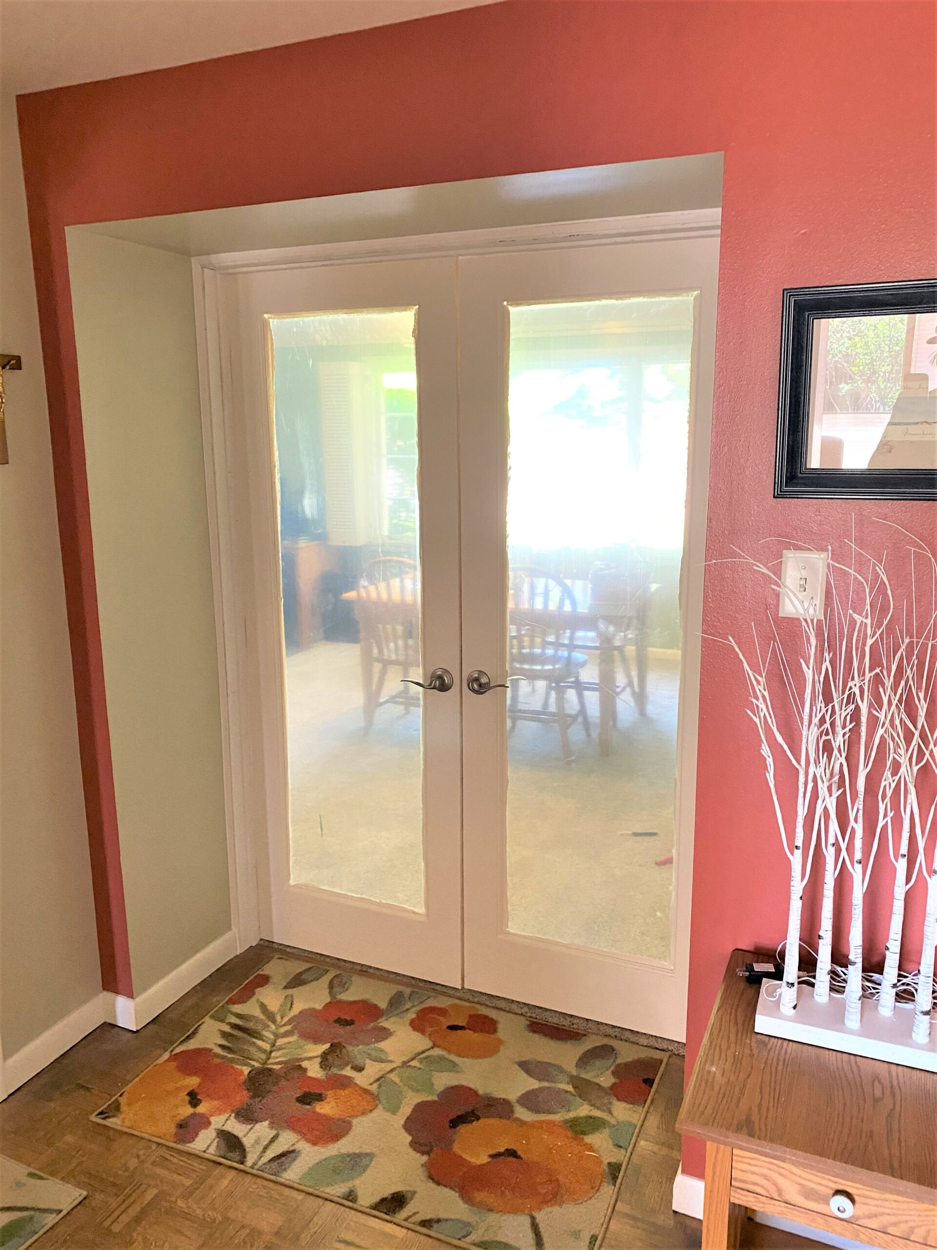 French doors with full pane windows and floral floor mat