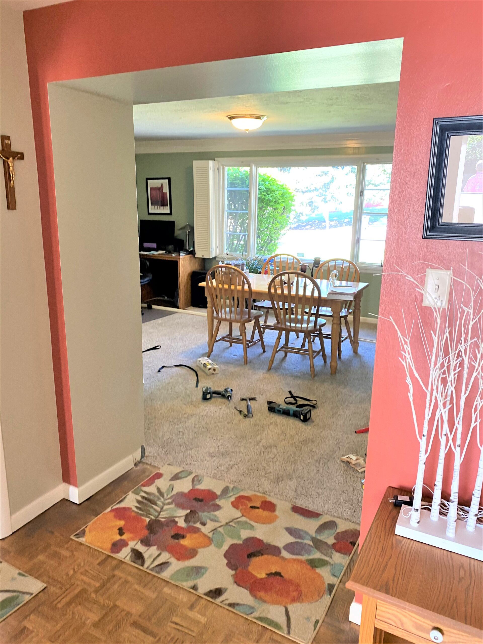 Walkway between kitchen and dining room with floral rug, pine table with 4 chairs, and window