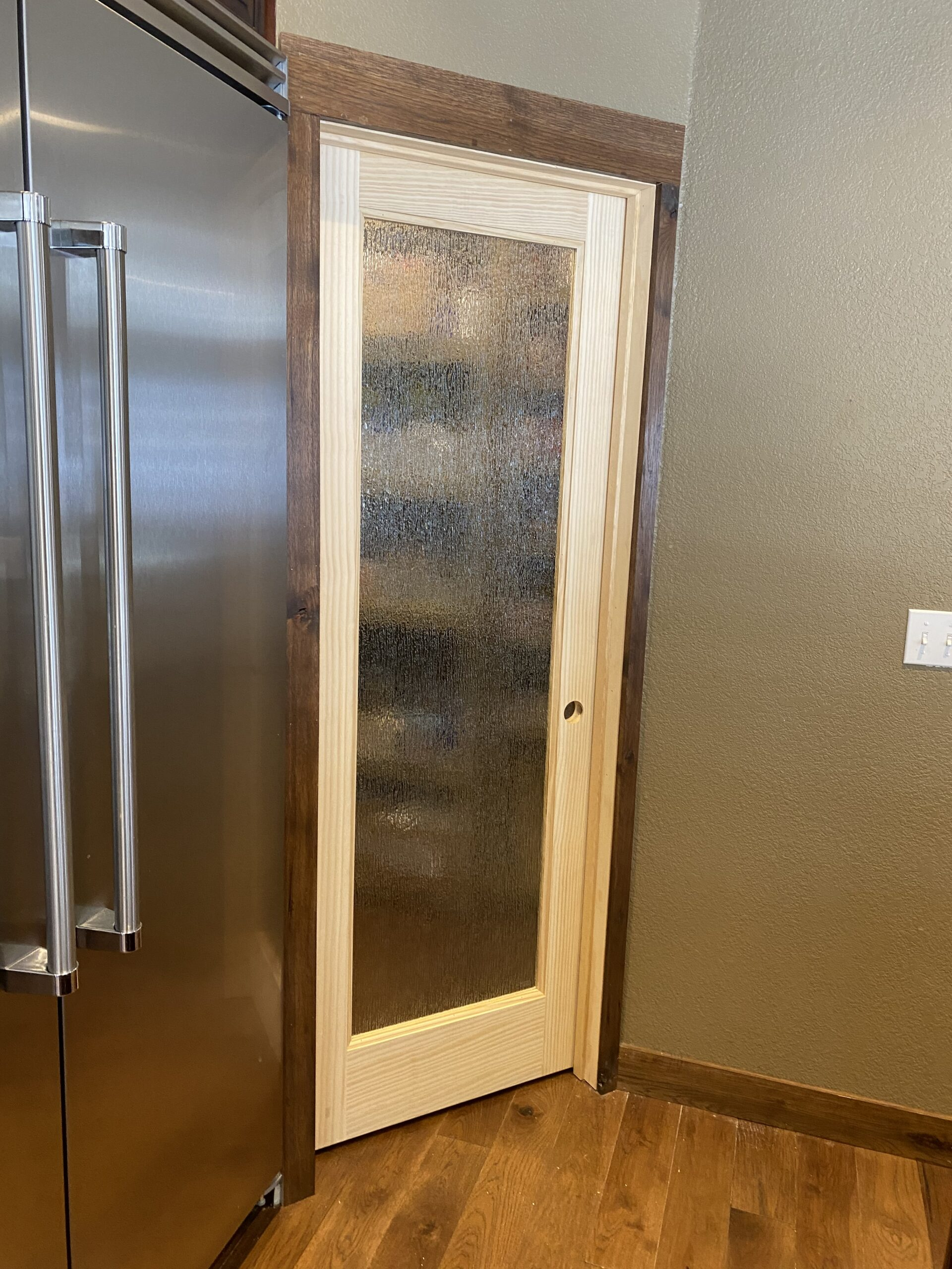 On right of stainless steel refridgerator is pine wood framed door with full pane of obscurity glass