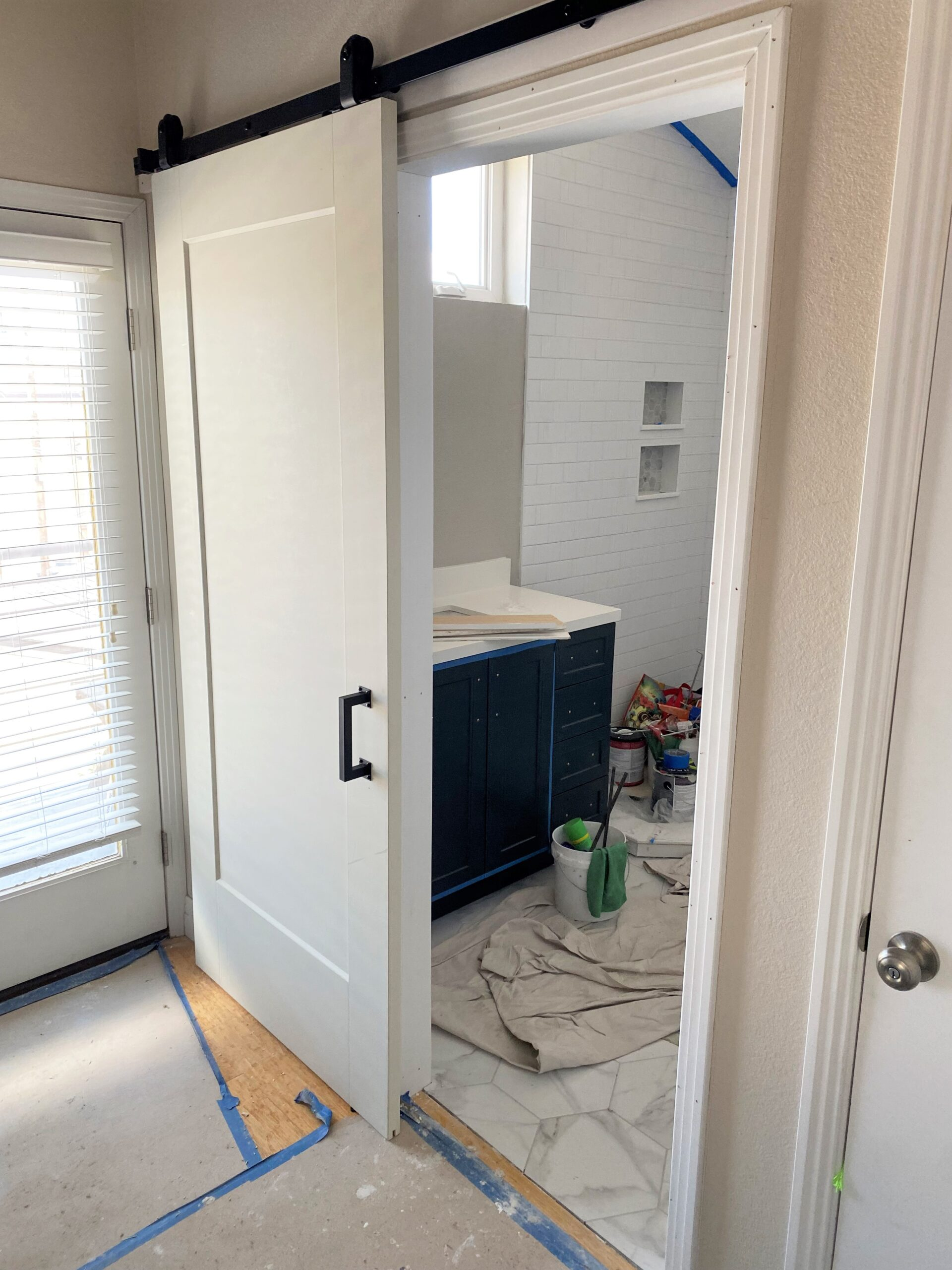 AFTER The finished trim and barn door installation for this bathroom entrance
